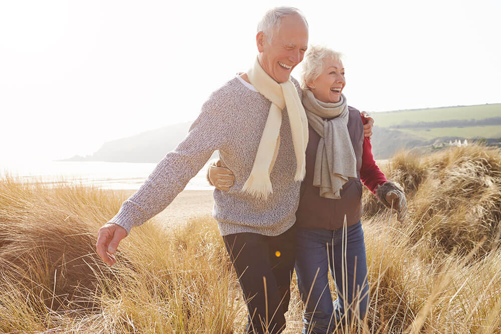 Smiling older couple walking arm in arm through the grass with green hills and a beach in the background