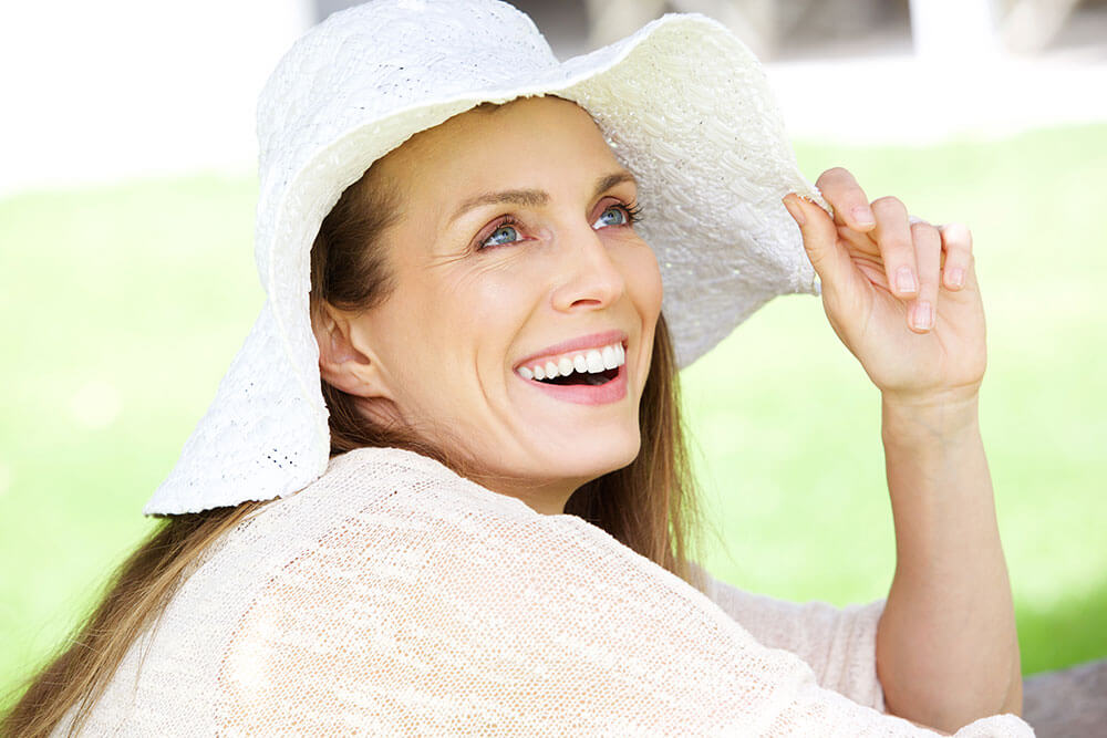 Smiling woman wearing a floppy white hat and white shirt