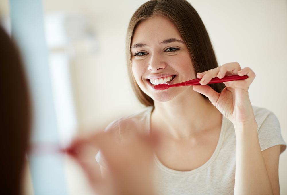 young woman brushing her teeth in mirror