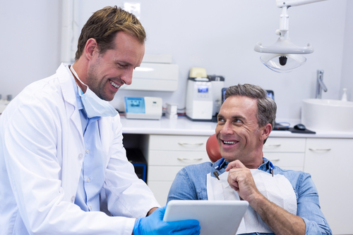 dentist and male patient viewing results on a digital tablet and smiling